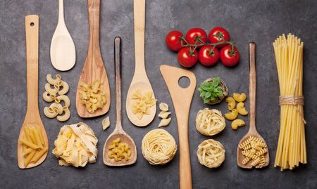Various pasta in spoons. Top view flat lay