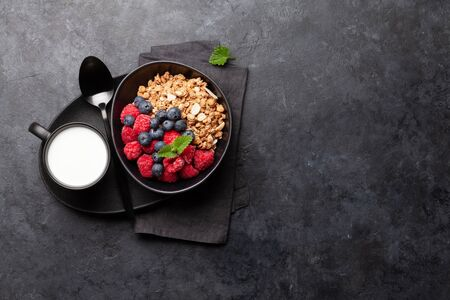 Healthy breakfast with homemade granola with yogurt and fresh berries on stone background. Top view with copy space