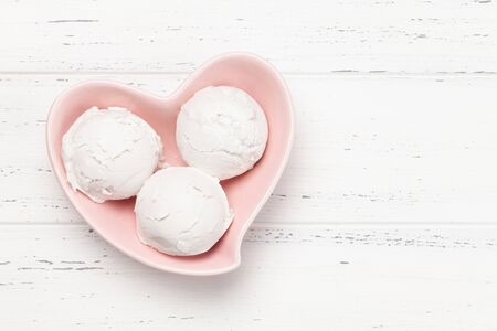 Vanilla ice cream scoops in heart shaped bowl on wooden background. Top view with copy space. Flat lay Banque d'images