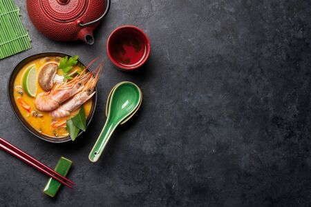 Tom yum traditional thai soup with seafood, mushrooms, coconut milk and hot spices. With green tea pot and bowl. Top view with copy space