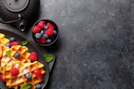 Delicious belgian waffles with ice cream and summer berries and breakfast tea. Top view with copy space Stock Photo