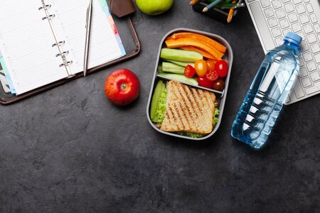 Healthy lunch box with sandwich and vegetables on office table. Top view with copy space. Flat lay