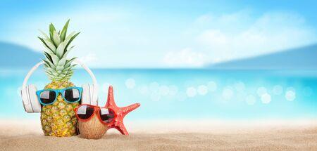 Tropisches Sommermeer mit funkelnden Wellen, Ananas und Kokosnuss mit Sonnenbrille und Kopfhörern am heißen Sandstrand. Reise- und Urlaubskonzept mit Kopierraum