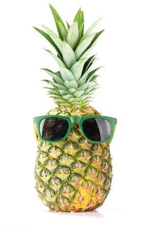 Reife Ananas mit Sonnenbrille auf weißem Hintergrund. Reise- und Urlaubskonzept