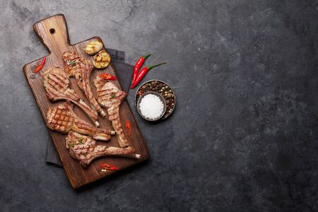 Grilled lamb ribs on cutting board. Hot rack of lamb with spices and condiments. Top view on stone table with copy space Archivio Fotografico
