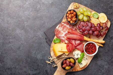 Cheese, meat, grapes and olives antipasto. Appetizer selection on wooden board. Top view with copy space. Flat lay Фото со стока