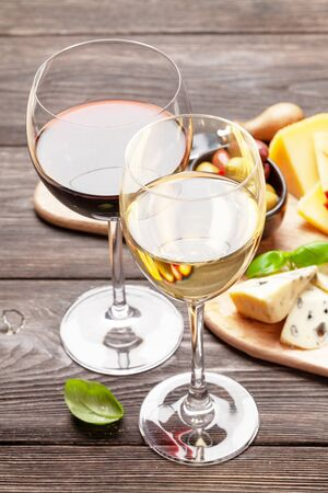 Red and white wine glasses in front of cheese, meat, grapes and olives antipasto. Appetizer selection Foto de archivo