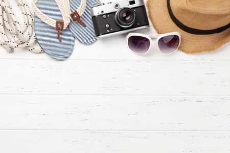 Summer vacation items and accessories. Flip flops, sunglasses, camera and sun hat on wooden table. Top view flat lay with copy space Фото со стока