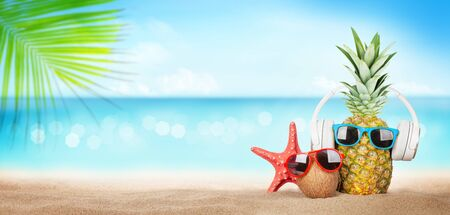Summer tropical sea with sparkling waves, pineapple and coconut with sunglasses and headphones on hot sand beach. Travel and vacation concept with copy space Archivio Fotografico