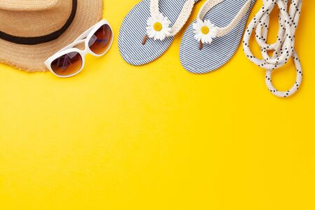 Summer vacation items and accessories. Flip flops, sunglasses and sun hat on yellow background. Top view flat lay with copy space 写真素材