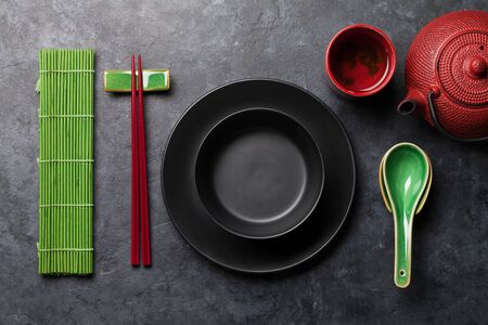 Japanese tea, empty plate and chopsticks on stone table. Asian food concept. Top view flat lay with copy space