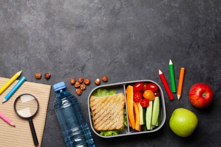 School lunch box and education stationery on stone table. Top view with copy space. Flat lay