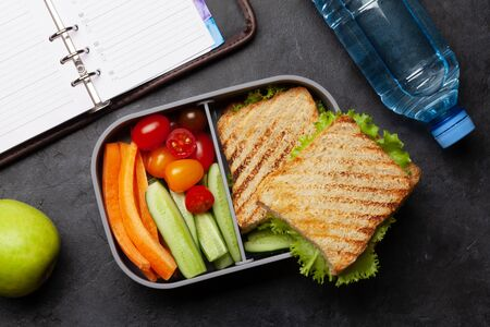 Healthy lunch box with sandwich and vegetables on office table. Top view. Flat lay