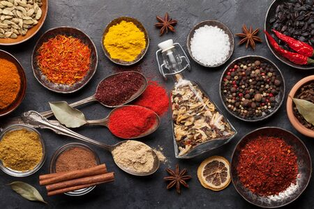 Various spices in bowls and spoons on dark stone table. Indian cuisine. Top view flat lay 写真素材