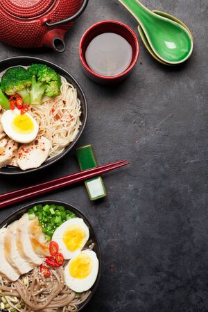 Asian noodle ramen soup with chicken, vegetables and eggs and herbal tea on stone background. Top view flat lay with copy space
