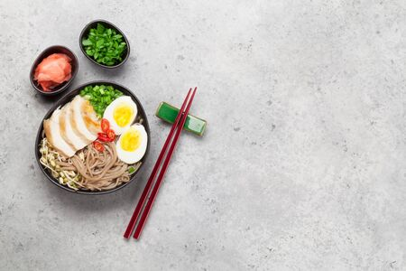 Asian noodle ramen soup with chicken, vegetables and eggs on stone background. Top view flat lay with copy space