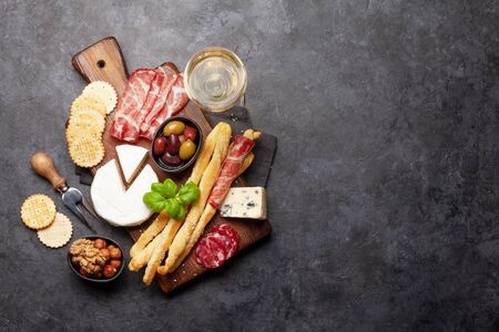 Cheese, meat and olives antipasto. Appetizer selection board and glass with white wine. Top view with copy space. Flat lay