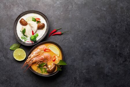 Tom Yum and Tom Kha traditional Thai soups with seafood, chicken, mushrooms, coconut milk and hot spices. Top view with copy space