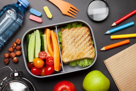 School lunch box and education stationery on stone table. Top view. Flat lay