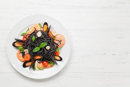 Black spaghetti pasta with seafood, tomatoes and basil. Top view flat lay with copy space