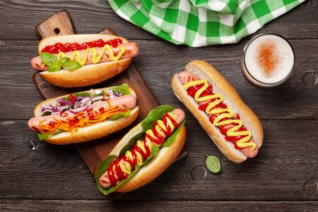 Various hot dog with vegetables, lettuce and condiments and beer glass on wooden background. Top view. Flat lay