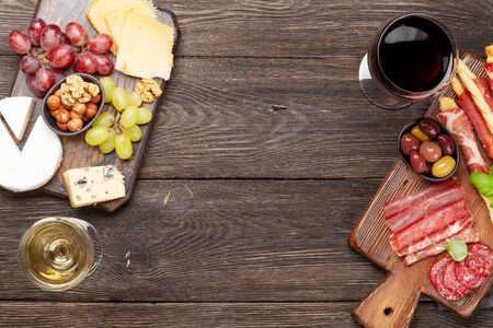 Cheese, meat, grapes and olives antipasto. Appetizer selection on wooden board and glasses with red and white wine. Top view with copy space. Flat lay 写真素材