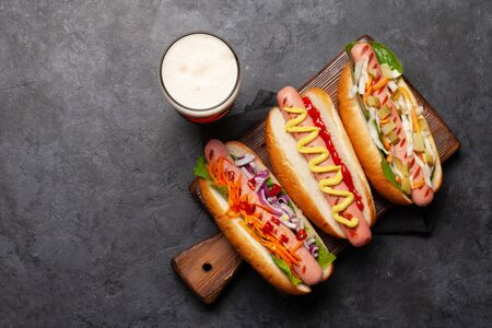 Various hot dog with vegetables, lettuce and condiments and beer glass on stone background. Top view with copy space. Flat lay