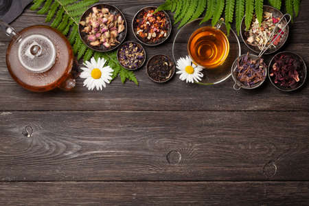 Various herbal dry tea, teapot and cup on wooden table. Top view with copy space. Flat lay