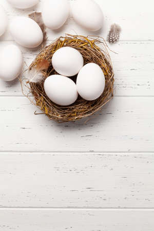 White chicken eggs in nest on wooden background. Top view with copy space. Flat lay 写真素材