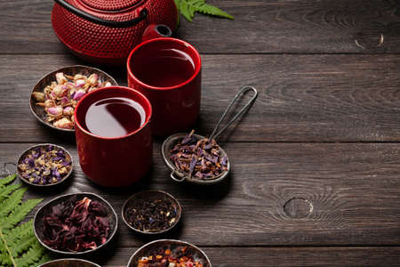 Various herbal dry tea, teapot and cup on wooden table. With copy space