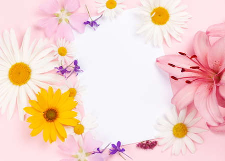 Garden flowers frame over pink background. Floral greeting card. Top view flat lay with copy space 写真素材