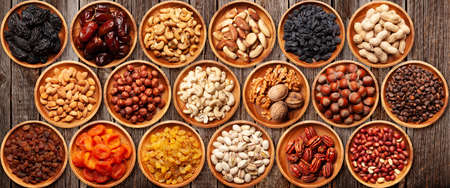 Various dried fruits and nuts on a wooden table. Top view flat lay