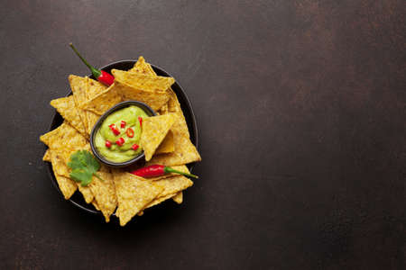 Mexican nachos chips with guacamole sauce. Top view flat lay on stone table with copy space
