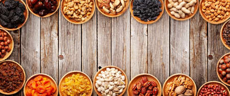 Various dried fruits and nuts on a wooden table. Top view flat lay with copy space