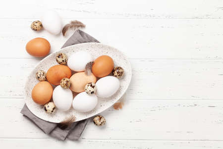 White, brown and quail eggs in plate on wooden background. Top view with copy space. Flat lay 写真素材