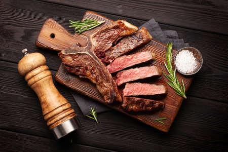 T-bone beef steak on cutting board. Top view flat lay