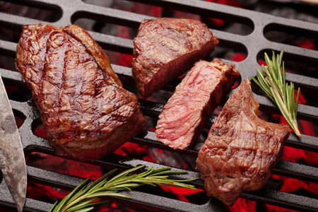 Beef steaks cooking on grill with spices and herbs