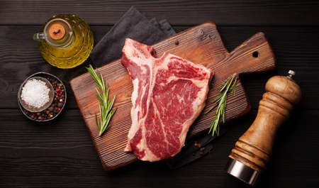 Raw T-bone beef steak on cutting board. Top view flat lay 写真素材