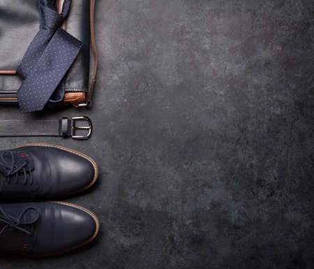 Set of men's classic clothes as tie, belt, shoes and bag on stone background with copy space. Top view flat lay Stock Photo