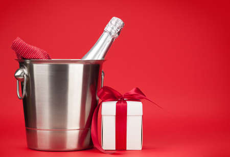 Champagne bottle in ice bucket and Valentine's day or Christmas gift box in front of red background with space for your greetings