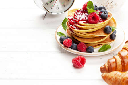 Delicious homemade pancakes with summer berries and coffee for breakfast. With copy space