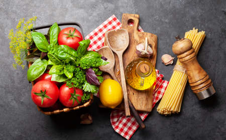 Italian cuisine ingredients. Garden tomatoes, pasta, herbs and spices. Top view Banco de Imagens