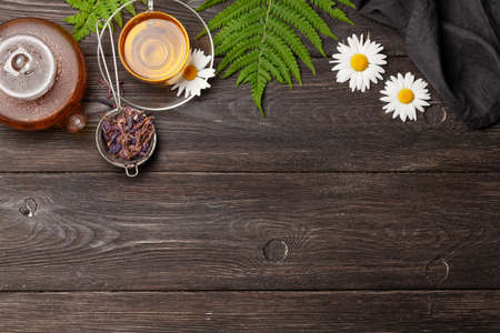 Herbal tea in teapot and cup on wooden table. Top view with copy space. Flat lay