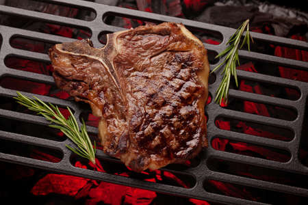 T-bone beef steak cooking on grill. Top view