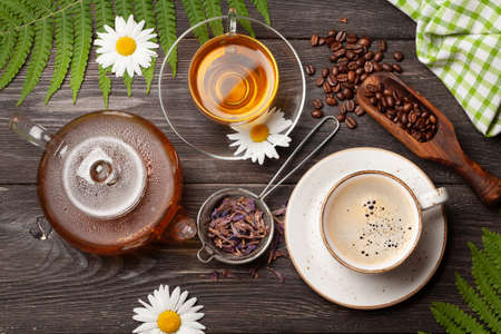 Herbal tea in teapot and cup and espresso coffee on wooden table. Top view. Flat lay