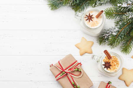 Eggnog. Traditional christmas cocktail, xmas gift boxes and gingerbread cookies on wooden table. Top view flat lay. With space for your greetings 免版税图像