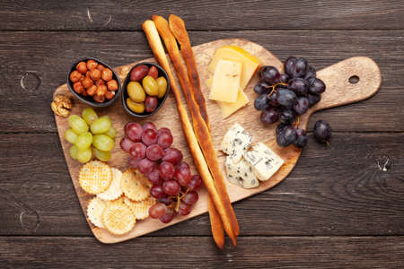 Cheese, grapes and olives antipasto. Appetizer selection on wooden board. Top view. Flat lay