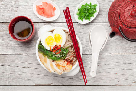 Asian noodle ramen soup with chicken, vegetables and eggs and herbal tea on wooden background. Top view flat lay