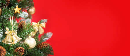 Christmas greeting card with decorated fir tree over red backdrop and copy space for your xmas greetings