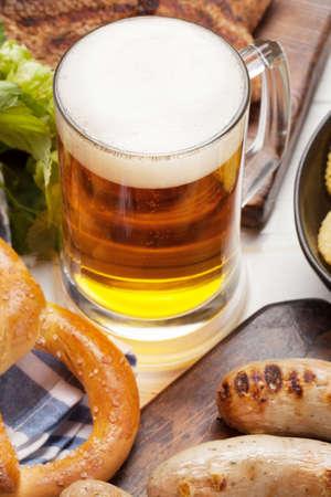 Oktoberfest set. Pretzels, sausages, meat and lager beer mug on wooden board 免版税图像
